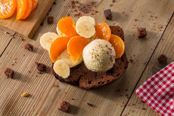 Brownie con helado y frutas